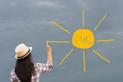 Woman drawing or painting sun onto grey sky royalty free stock images