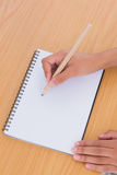 Woman drawing on a paper on a desk Royalty Free Stock Photography
