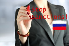 Woman drawing a phrase stop  sanctions  by a  red pen . Royalty Free Stock Image