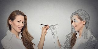 Woman drawing a picture, sketch of herself. Create yourself, your future destiny, image, career concept. Attractive young woman drawing a picture, sketch of Royalty Free Stock Photography