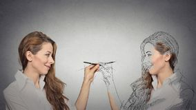 Woman drawing a picture, sketch of herself. Create yourself, your future destiny, image, career concept. Attractive young woman drawing a picture, sketch of Royalty Free Stock Image