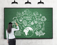 Woman drawing renewable energy sources sketches at blackboard Royalty Free Stock Photography