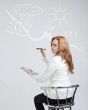 Woman drawing schematic representation of the. Young woman drawing schematic representation of the water cycle in nature Royalty Free Stock Images