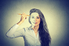 Woman drawing self portrait with pencil. Beautiful woman drawing self portrait with pencil Royalty Free Stock Photos
