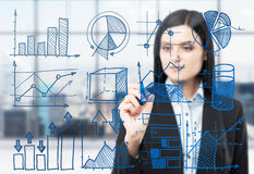 A woman is drawing some business charts on the glass screen. Modern panoramic office with New York view in blur on the ba. A brunette woman is drawing some Stock Image