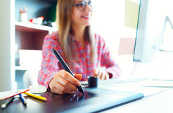 Woman drawing something on graphic tablet at the home office Royalty Free Stock Images