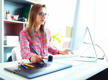 Woman drawing something on graphic tablet at the home office. Young artist drawing something on graphic tablet at the home office Royalty Free Stock Photos
