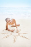 Woman drawing a sun sign on the sand Royalty Free Stock Photo