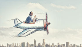 Woman in drawn airplane. Young funny woman flying in air in drawn airplane Stock Photography