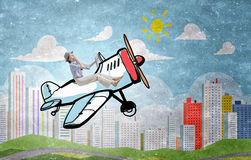 Woman in drawn airplane. Young funny woman flying in air in drawn airplane Stock Photos
