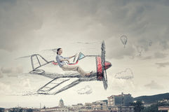 Woman in drawn airplane. Young funny woman flying in air in drawn airplane Royalty Free Stock Photos
