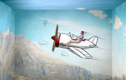 Woman in drawn airplane. Young funny woman flying in air in drawn airplane Royalty Free Stock Photo