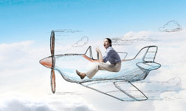 Woman in drawn airplane. Young funny woman flying in air in drawn airplane Stock Image