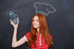 Woman in drawn chef hat holding drawing cupcake over blackboard. Charming happy redhead young woman in drawn chef hat holding drawing cupcake over blackboard Stock Photography