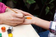 Woman draws carrot on girl hand Stock Image
