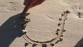 The woman draws heart in the sand stock video footage