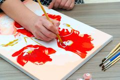 Woman draws a painting with a brush and paints. A woman`s hand draws a painting with a brush and paints Royalty Free Stock Images