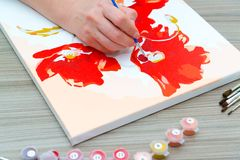 Woman draws a painting with a brush and paints. A woman`s hand draws a painting with a brush and paints Royalty Free Stock Photos