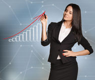 Woman draws red arrow of growth over bar graph.  Stock Photo