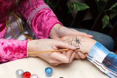 woman draws spider on girl hand Stock Photos