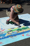 Woman draws on the street with chalk Stock Image
