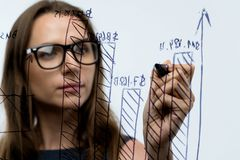 Woman draws various growth charts, calculating prospects for suc. Businesswoman draws various growth charts, calculating prospects for success in a modern glass Royalty Free Stock Image
