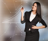 Woman draws white arrow of growth over bar graph Royalty Free Stock Images