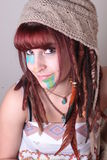 Woman with Dread Locks, Feather, and PaintPortriat. A woman with dread locks with string, wearing a hat, and necklaces Royalty Free Stock Image