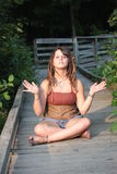 Woman with Dread Locks Meditating. A woman with dread locks with string, necklaces, and a nose piercing sitting meditating on a board walk. Her legs are covered Royalty Free Stock Image