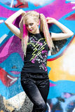 Woman with dreadlocks. Young woman standing at graffitti wall Royalty Free Stock Image