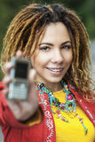Woman with dreadlocks showing mobile phone Stock Photo
