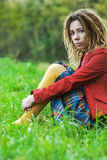 Woman with dreadlocks sits grass Royalty Free Stock Images