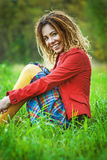 Woman with dreadlocks sitting on grass Stock Photos