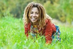 Woman with dreadlocks sitting on grass Stock Photo