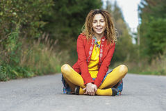 Woman with dreadlocks sitting in lotus position Royalty Free Stock Images