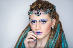 Woman with dreads. Young beautiful girl woman with brown, blue dreadlocks. Stylish volume hair-do, professional make-up art, rhinestones crystals. Large tiara Stock Images