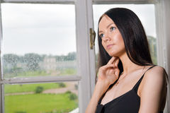 Woman dream of something. Young beautiful woman dream of something at her mansion house near window Royalty Free Stock Photo