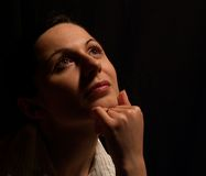 Woman dreaming. Beautiful girl on black background looking up and dreaming Royalty Free Stock Images