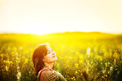 Woman dreaming enjoying sunlight in canola field Royalty Free Stock Photo