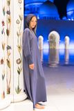Woman dreaming at the grand mosque of Sheikh Zayed Mosque in Abu Dhabi wearing abaya, paranja in night time. Travelling. Enjoy Royalty Free Stock Photo