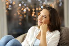 Woman dreaming at home with lights in background. Candid woman dreaming sitting on a couch in the living room at home with little lights in the background royalty free stock photo
