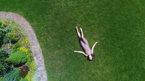 Woman dreaming lying on grass, aerial view, rotating drone fly above garden lady. Stock footage stock footage