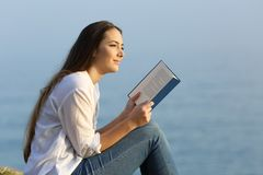Woman dreaming reading a book on the beach Royalty Free Stock Image