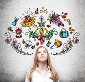 Woman is dreaming about sopping. Colourful shopping icons are drawn on the wall. Concrete background. Stock Image