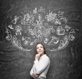 Woman is dreaming about sopping. Shopping icons are drawn on the black chalkboard. Royalty Free Stock Photos