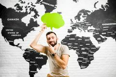 Woman dreaming about vacation. Man holding a colorful bubble above the head sitting at the office with world map on the background dreaming about traveling Royalty Free Stock Image