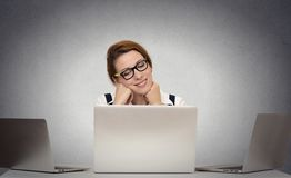 Woman dreaming while working on multiple computers Royalty Free Stock Photography
