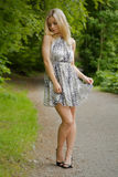 Woman with a dress along a road in a park Stock Photo