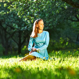 Woman in dress among apple blossoms Royalty Free Stock Image