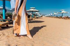 Woman walks barefoot on the beach royalty free stock photos